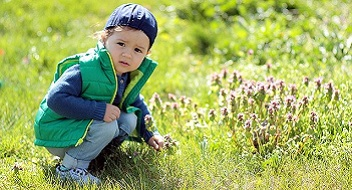 toddler playing in grass_kids potential language therapy_352x190